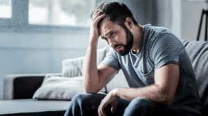 Distressed man sits in contemplative mood