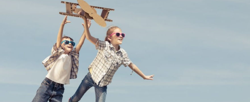 Kids fly cardboard plane outdoors