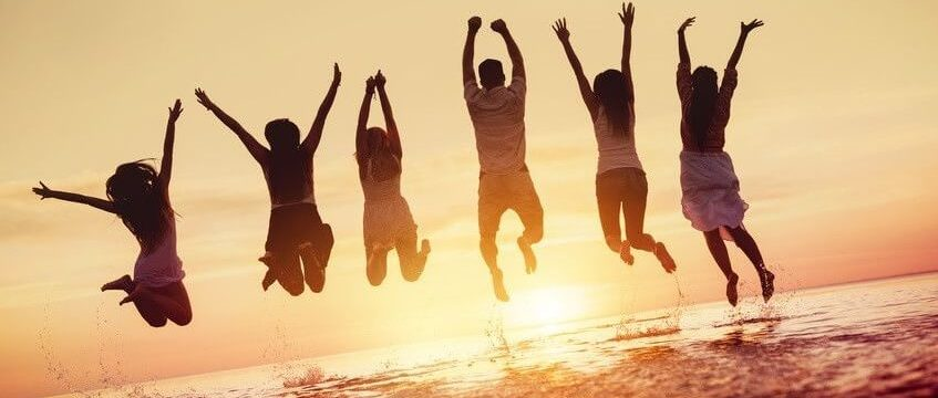 Young people jump for joy enoying beach sunset